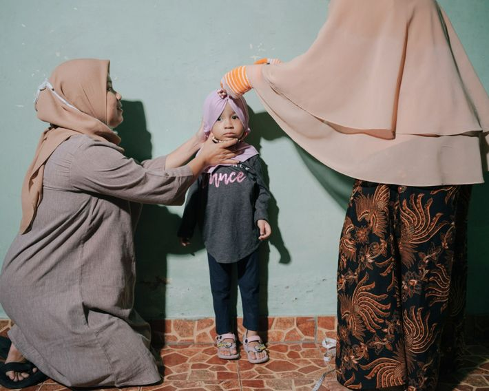 Roozmalinie, left, holds her 3-year-old daughter Aquilla, center, as she is measured by Kris Wati, right, ...