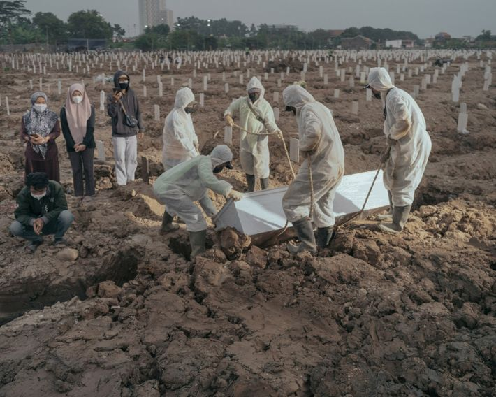 Workers lower a COVID-19 victim into the earth at Rorotan Public Cemetery on July 21, 2021. ...