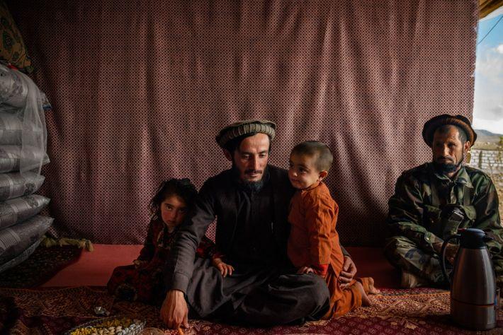 Qari Mehrabuddin, a pro-government militia commander, sits with two of his five children in his home ...