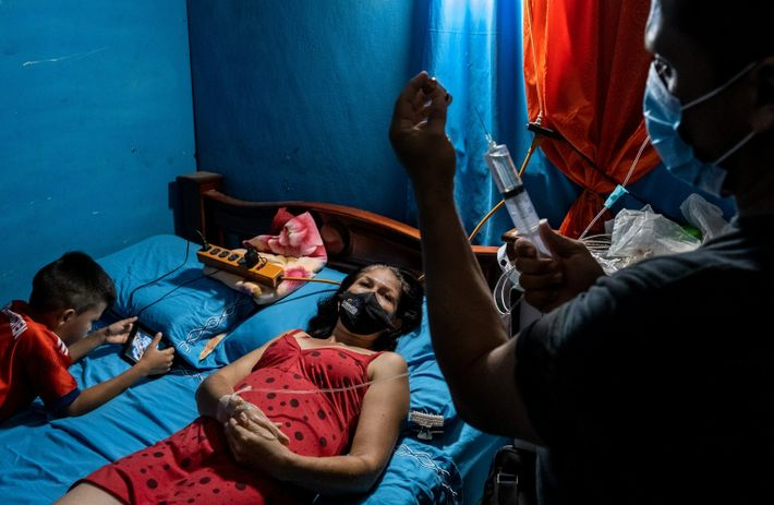 Marinelly Hernandez lies in bed next to her son as she receives treatment for COVID-19 at ...