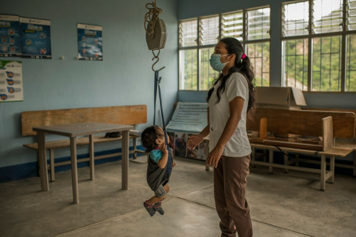 A nurse places Floria on a scale at the community health outpost. She clocks in at ...