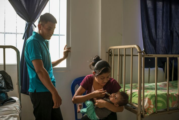 Berta Vásquez feeds her son, Elman, as her husband looks on. Vásquez is staying at the ...