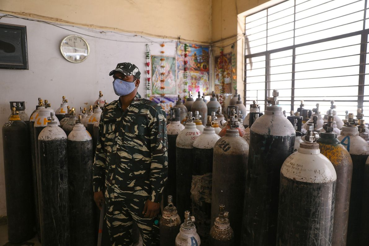 Indian Paramilitary personnel stands guard inside the oxygen depot as crowds waiting outside for long hours ...