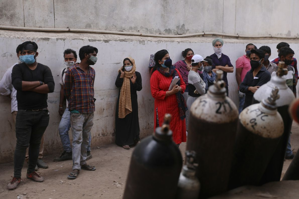 People wait in line inside the oxygen refilling plant for their turn to arrive in New ...