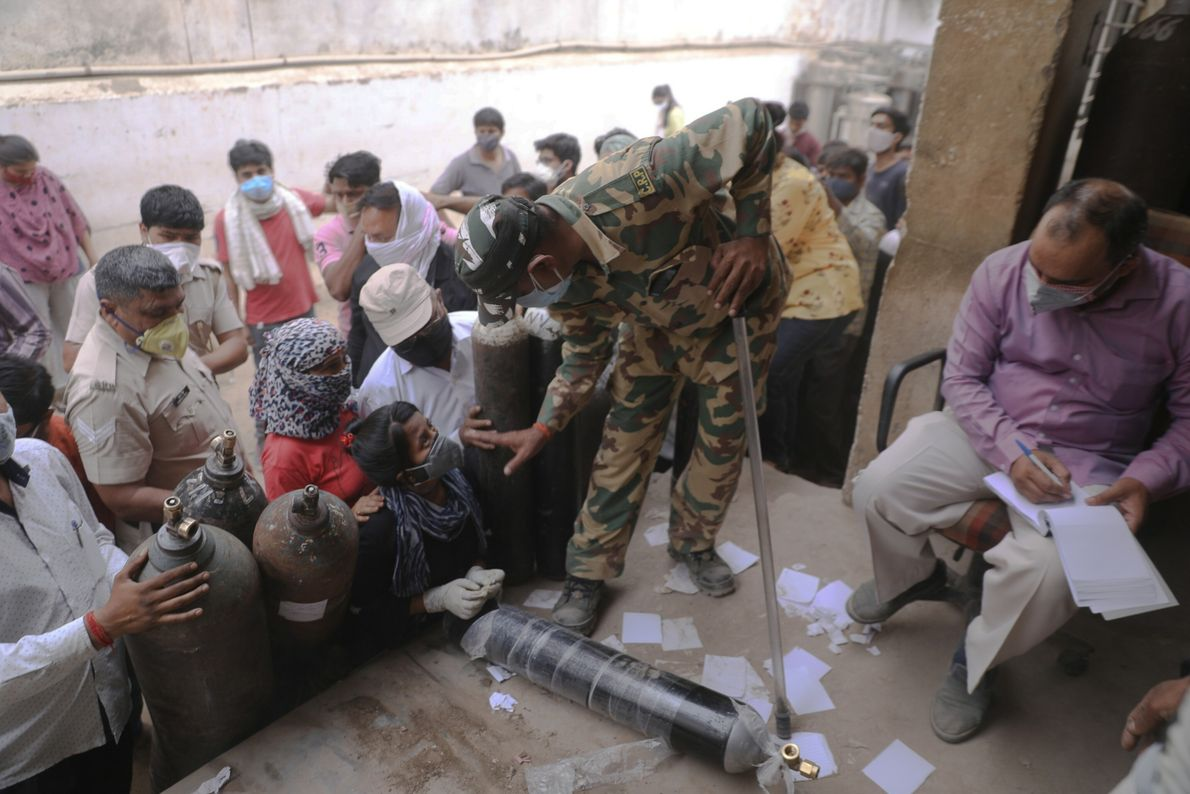 An Indian paramilitary personnel stands guard as people take tokens for refilling oxygen cylinders in New ...