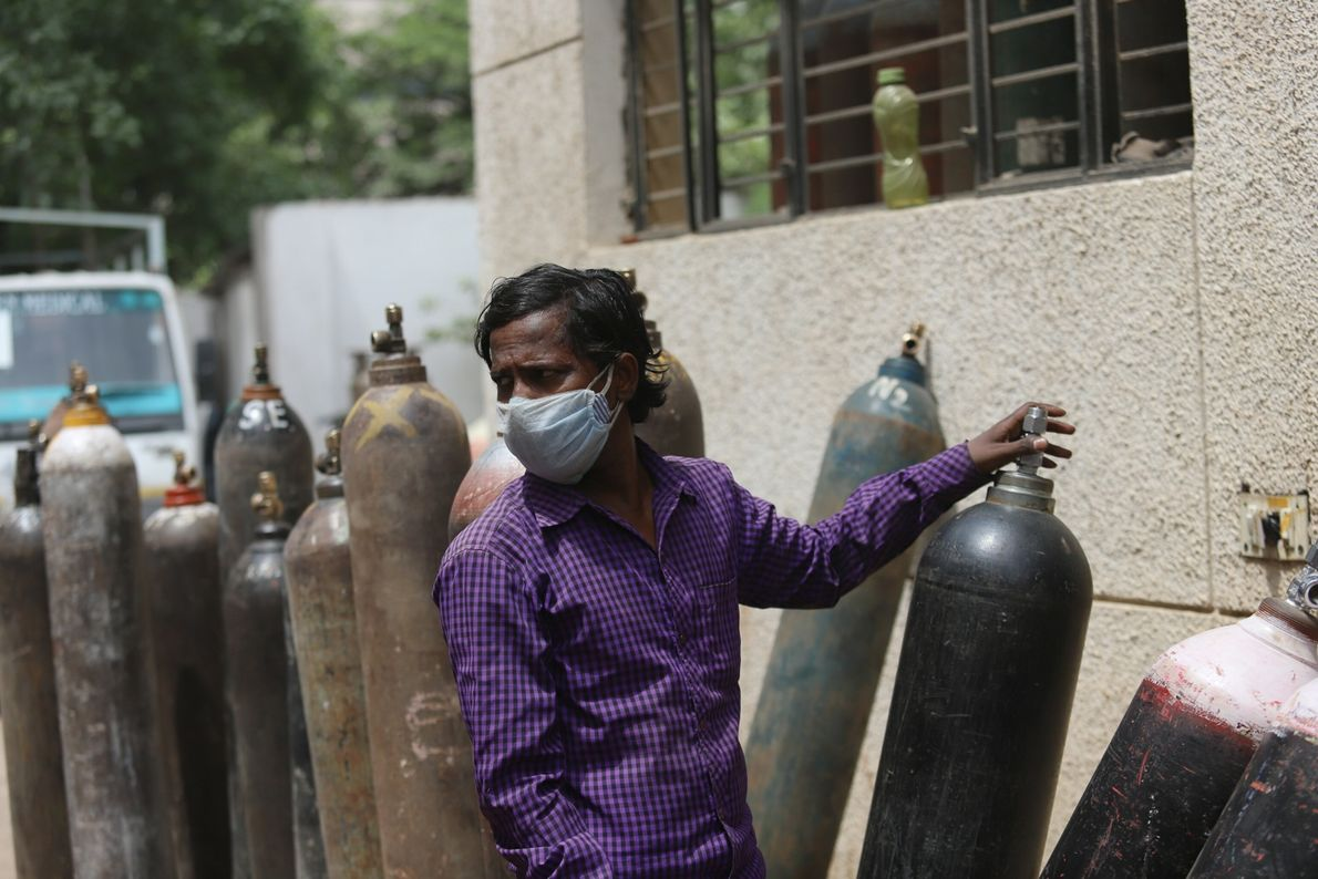 Mahesh Kumar waits patiently in line to refill an oxygen cylinder for his father outside refilling ...