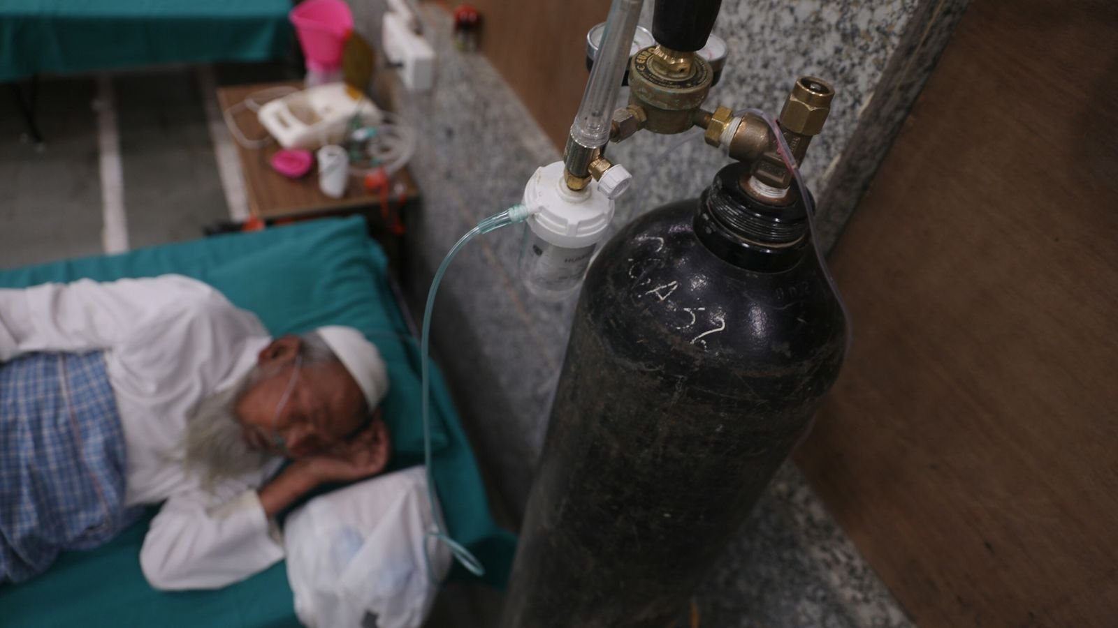 An old man rests with an oxygen mask on at the makeshift quarantine center at Jamia ...