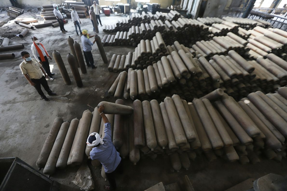 Workers move newly manufactured cylinders for transport at BPCL factory in Prayagraj, Uttar Pradesh, India, on ...