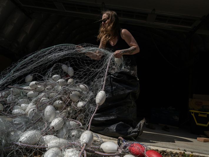 Susie Jenkins-Brito stacks nets into bags before the start of the season. Jenkins-Brito is a nurse ...