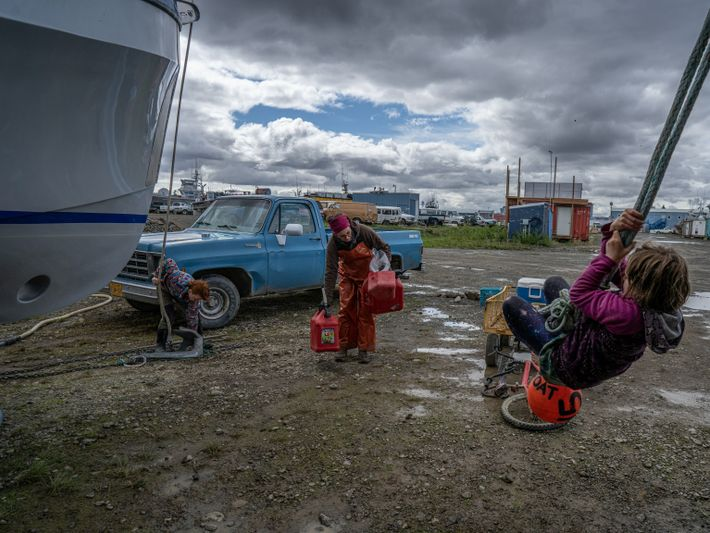 Rubis and Margaret Gervais play near their mother's boat in the PAF Marine Services boatyard while ...