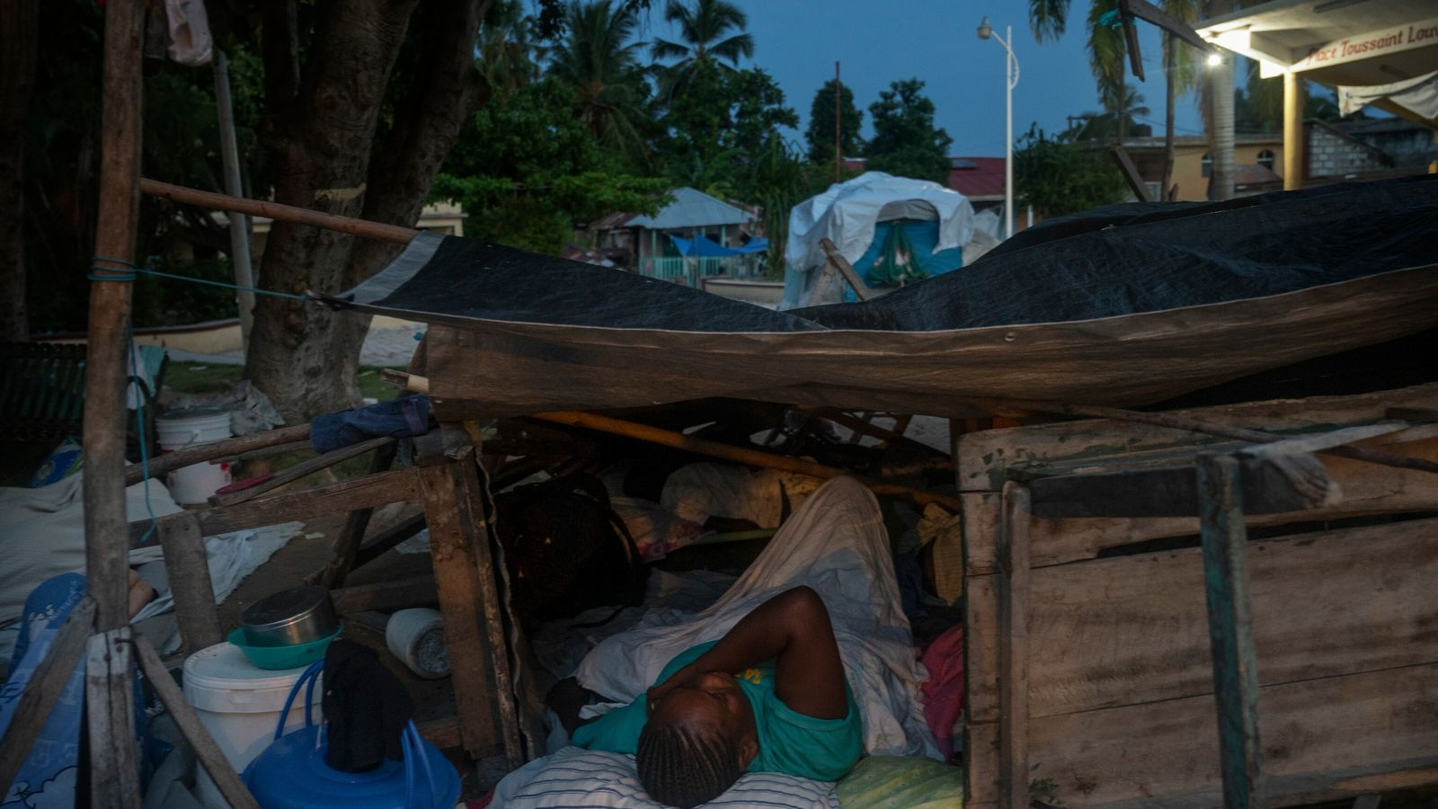 """A resident of Corail, Haiti, sleeps on the streets in a makeshift shelter. """"Most of this ..."""
