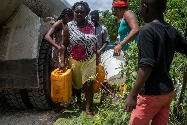 A woman wrestles jugs of water away from neighbors also desperate for their share. After the ...