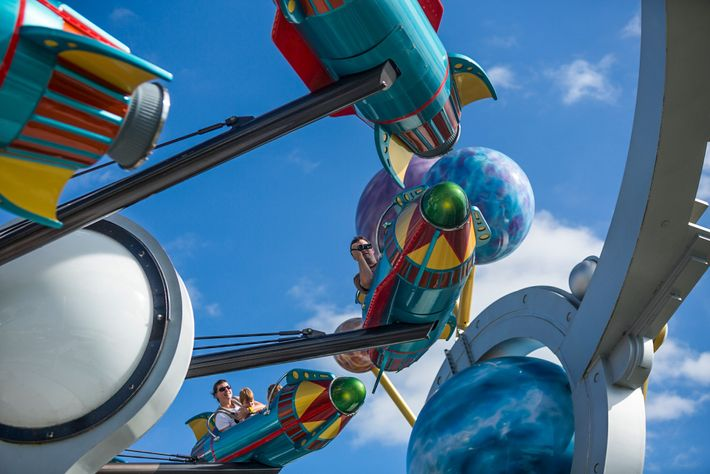 Tourists go for a spin on the Astro Orbiter ride at Disney World in Orlando, Florida. ...