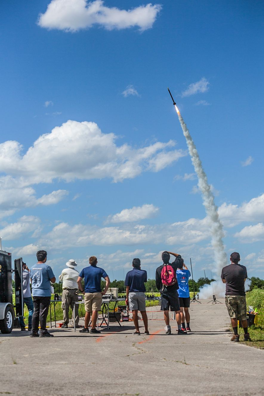 A small crowd gathers to watch a rocket launch at an amateur rocketry gathering in Palm ...