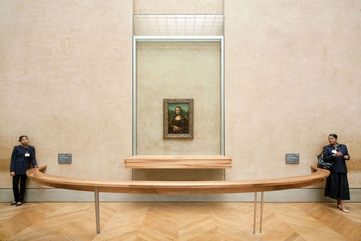 """Arguably the world's most famous work of art, the """"Mona Lisa"""" is now displayed behind thick ..."""