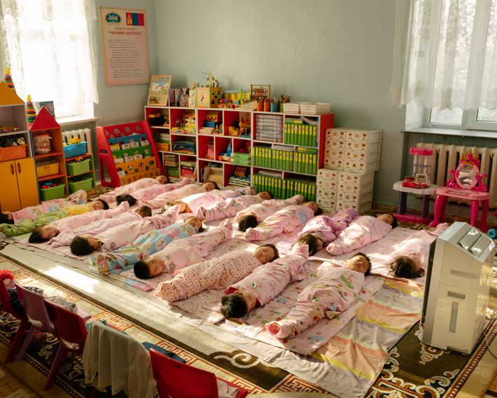 An air purifier stands watch over napping children at a kindergarten in the Bayanzurkh District. Young ...