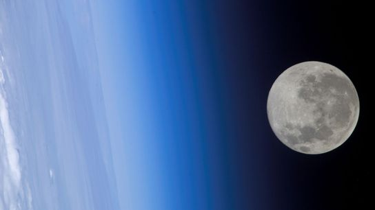 A full moon seems to brush Earth's atmosphere as seen from the International Space Station.