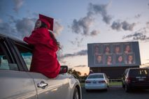 Senior class president Emma Olson attends her socially distanced high school graduation at a drive-in theatre ...