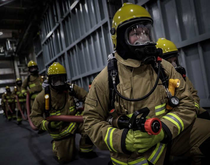 Firefighting crew use the ship's aircraft hangar for training.