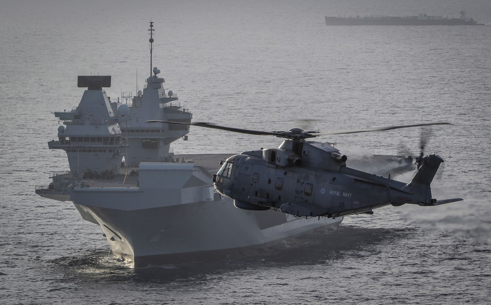 A Merlin Mk2 helicopter conducts trials during HMS Queen Elizabeth's North Atlantic crossing.
