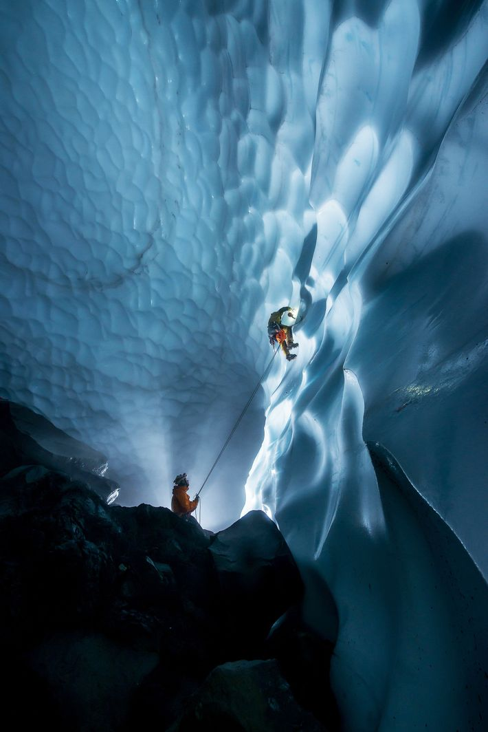 Eddy Cartaya climbs down an ice wall with the help of James Frystak, placing ablation markers ...