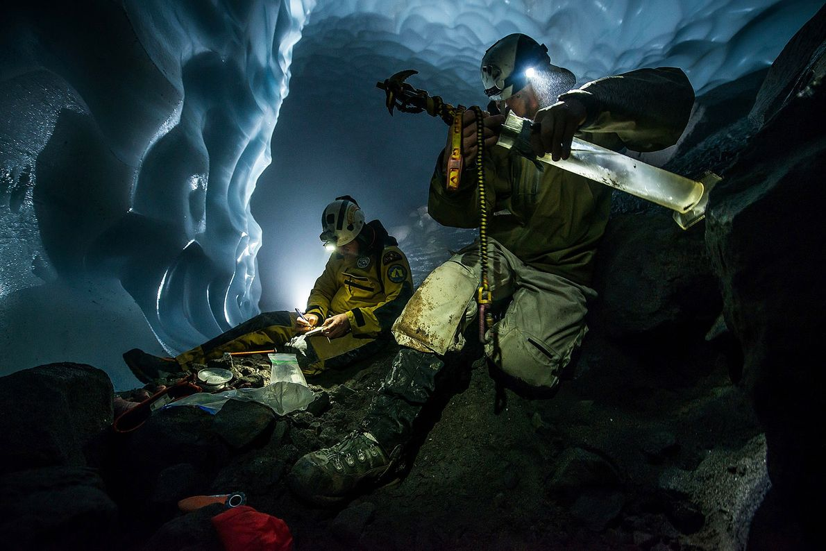 Eddy Cartaya, a team leader, measures ice density in a cave with Woody Peebles.