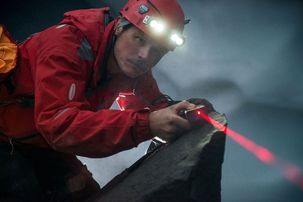 John Punches performs a mapping measurement inside a Mount Rainier ice cave.