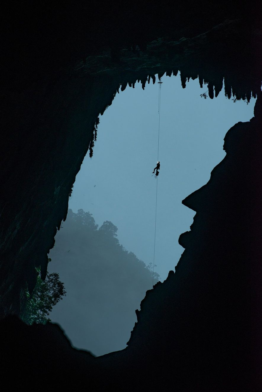 An expedition team member climbing toward the roof of Deer Cave dangles above a silhouette that looks like Abraham Lincoln. The sharp presidential profile is a natural feature of the limestone and one of the cave system's many curiosities.