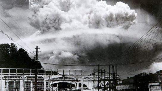 A large mushroom cloud still looms in the sky over Nagasaki 15 minutes after the atomic ...