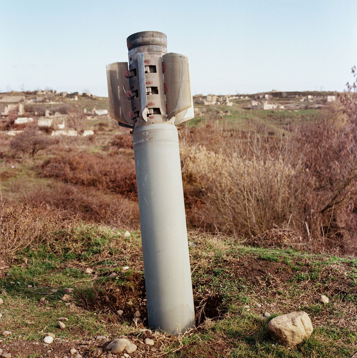 """An unexploded Russian-made """"Smerch"""" rocket sticks out of the ground in the Fizuli district, which saw ..."""