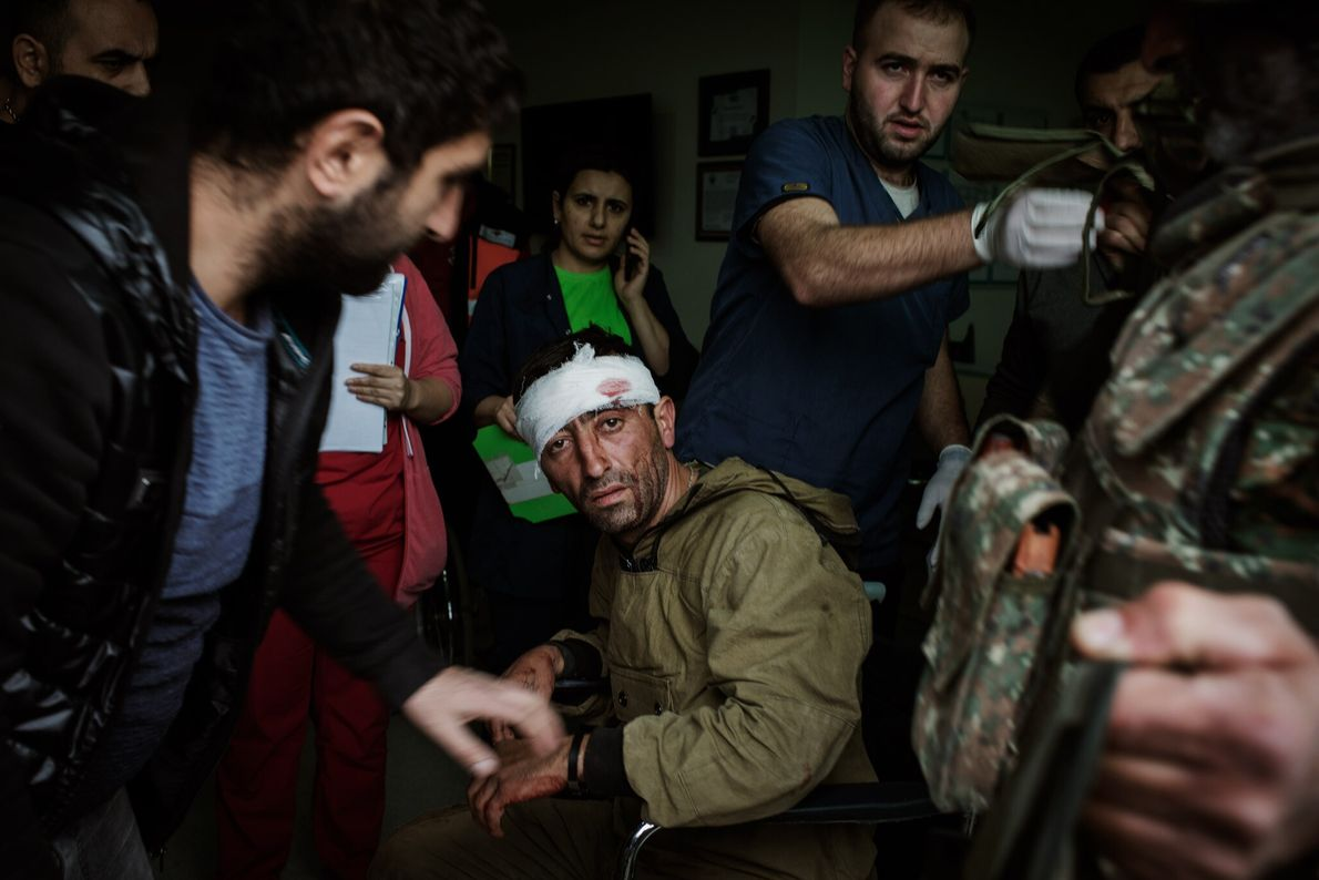Medical professionals at the Republican Medical Center in Stepanakert tend to a wounded combatant fighting on ...