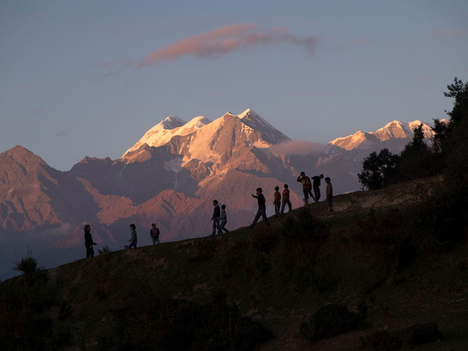 Children play soccer on a slope against a backdrop of the sunlit peaks of Nanda Devi, ...