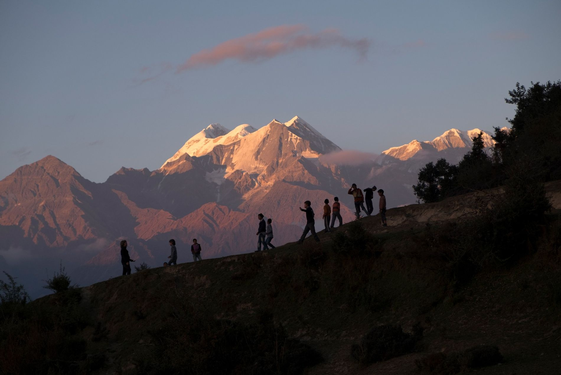 Children play soccer on a slope against a backdrop of the sunlit peaks of Nanda Devi, ...