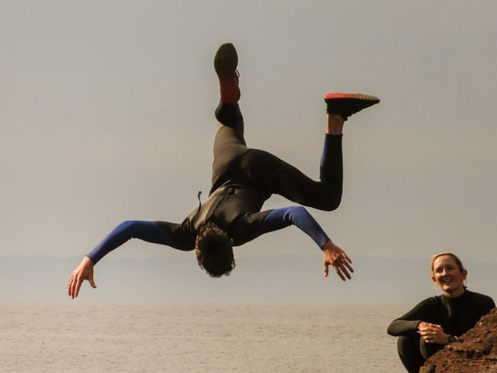 Robbie Clark performs a forward flip into the mouth of Seacliff Harbour.