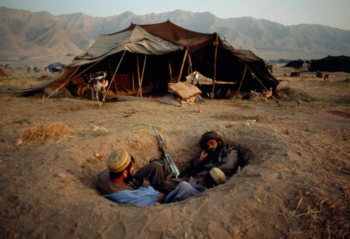 Two Afghan fighters seek scant cover during the conflict in 2001. The United States invaded Afghanistan ...