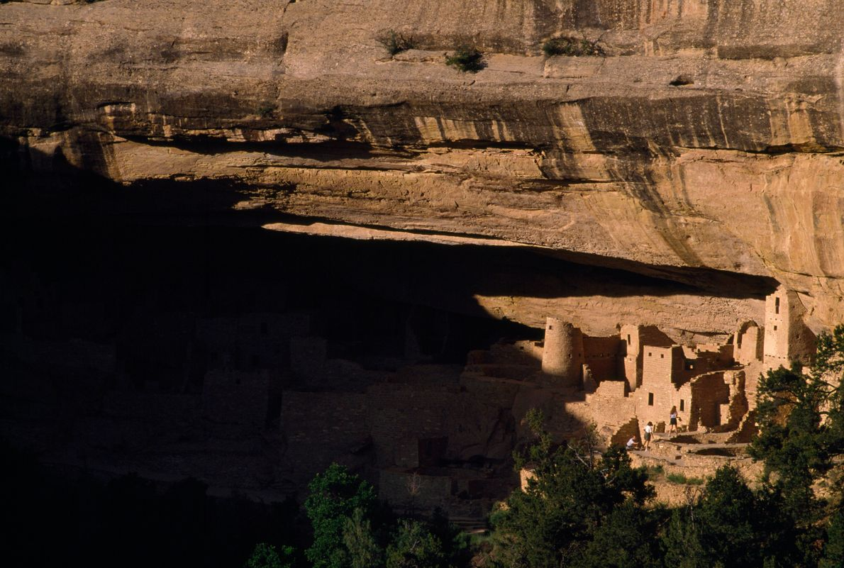 The sun lights up cliff dwellings at Mesa Verde National Park in Colorado. Ancestral Puebloans built ...