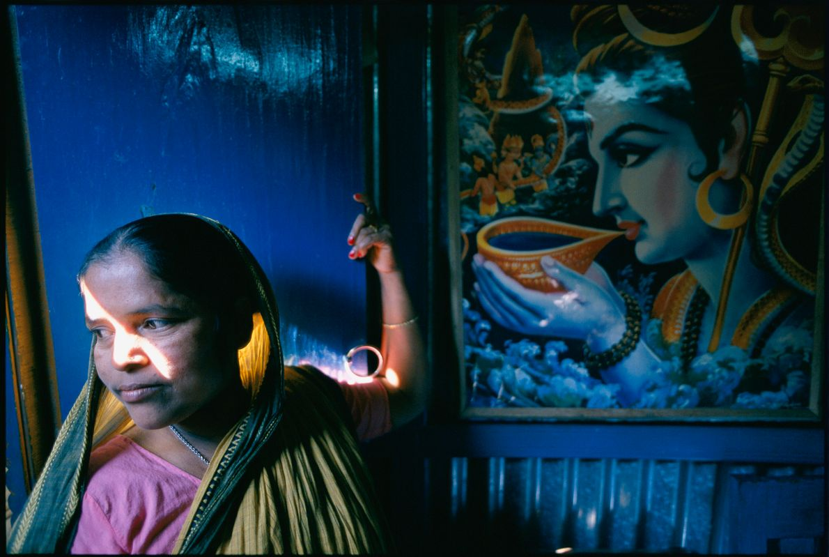 A widow in Bangladesh stands in her family's home, which she paid for with money from ...