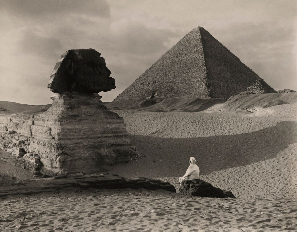 A man sits in front of the Great Sphinx in Giza, Egypt. This photograph in the ...