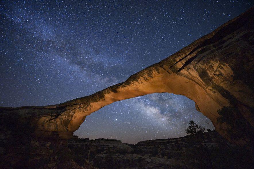 A starry night gleams above Owachomo Bridge in Natural Bridges National Monument, Utah.