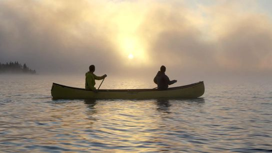 Two paddlers glide along Whitewater Lake in Wabakimi Provincial Park