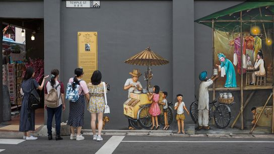 Tourists on Temple street in Chinatown take in a mural of a Chinese opera by artist ...