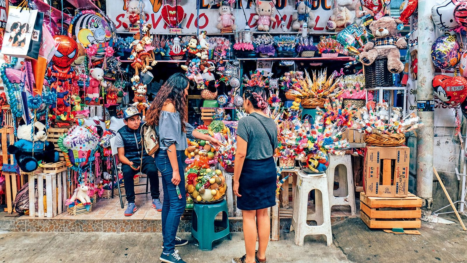 Tourists browsing the offerings at a colourful stall in Mercado Jamaica, one of the largest flower ...