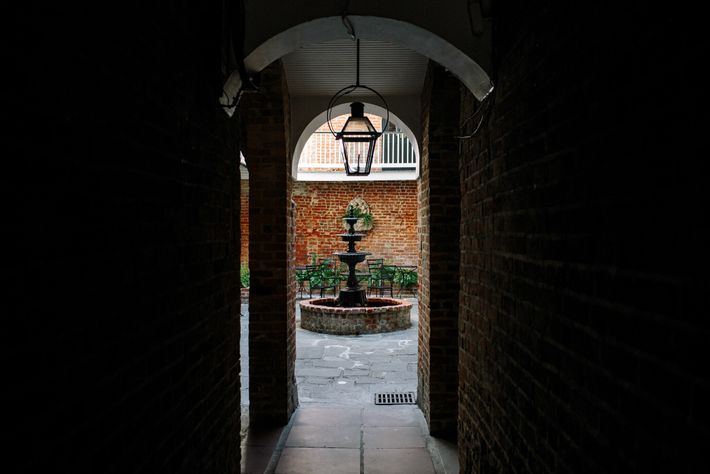 A brick passageway leads to a private courtyard in the historic French Quarter of New Orleans.