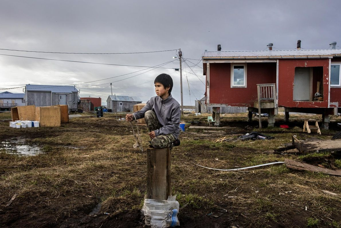 Reese John plays with his slingshot on a piling from a recently demolished home in Newtok. ...