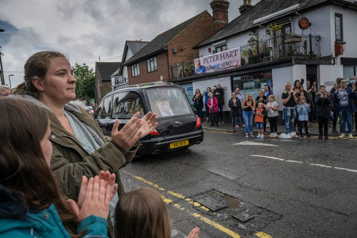 Hundreds of friends, family, and supporters of the NHS line the streets as the coffin of ...