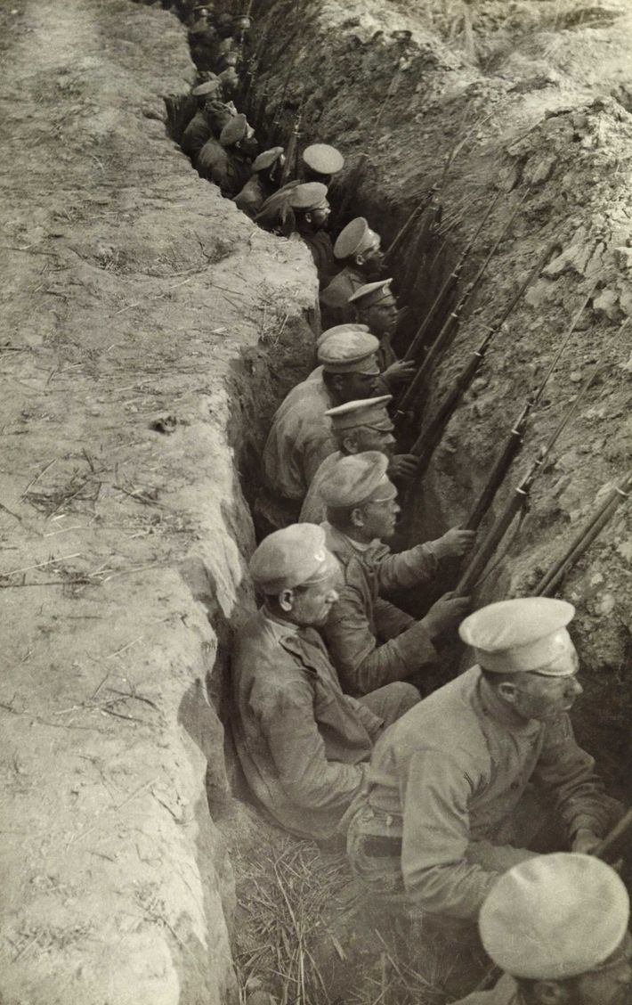Photographed in 1917, an endless line of Russian soldiers sit patiently in a trench as they ...