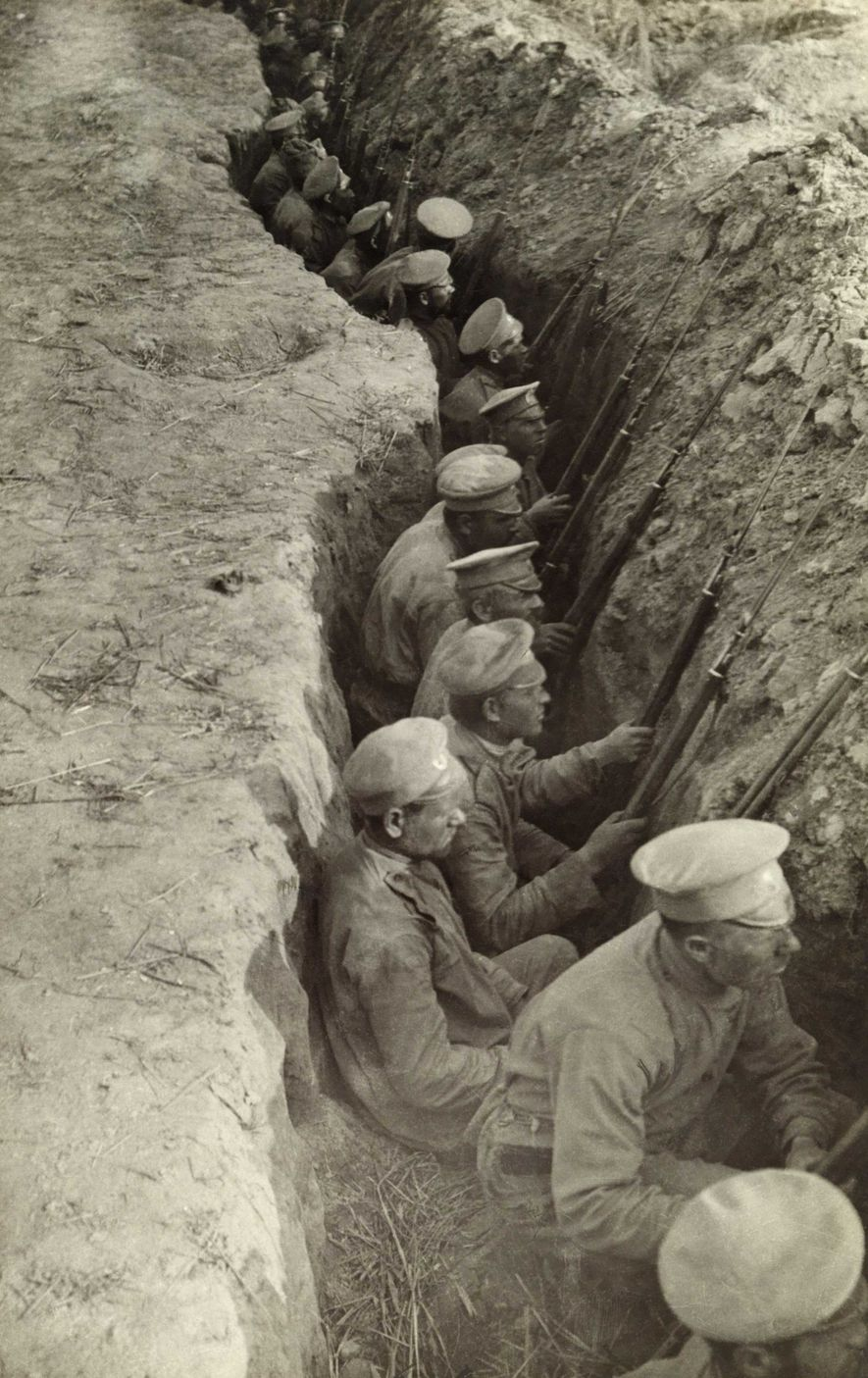 Photographed in 1917, an endless line of Russian soldiers sit patiently in a trench as they anticipate a German attack.
