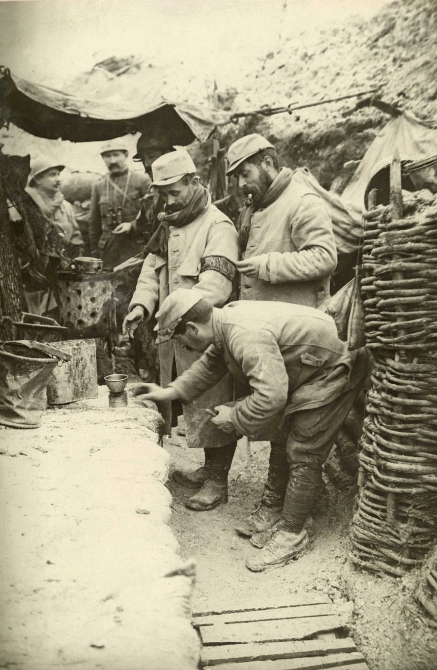 French soldiers warm up glasses of wine to drink in the trenches.