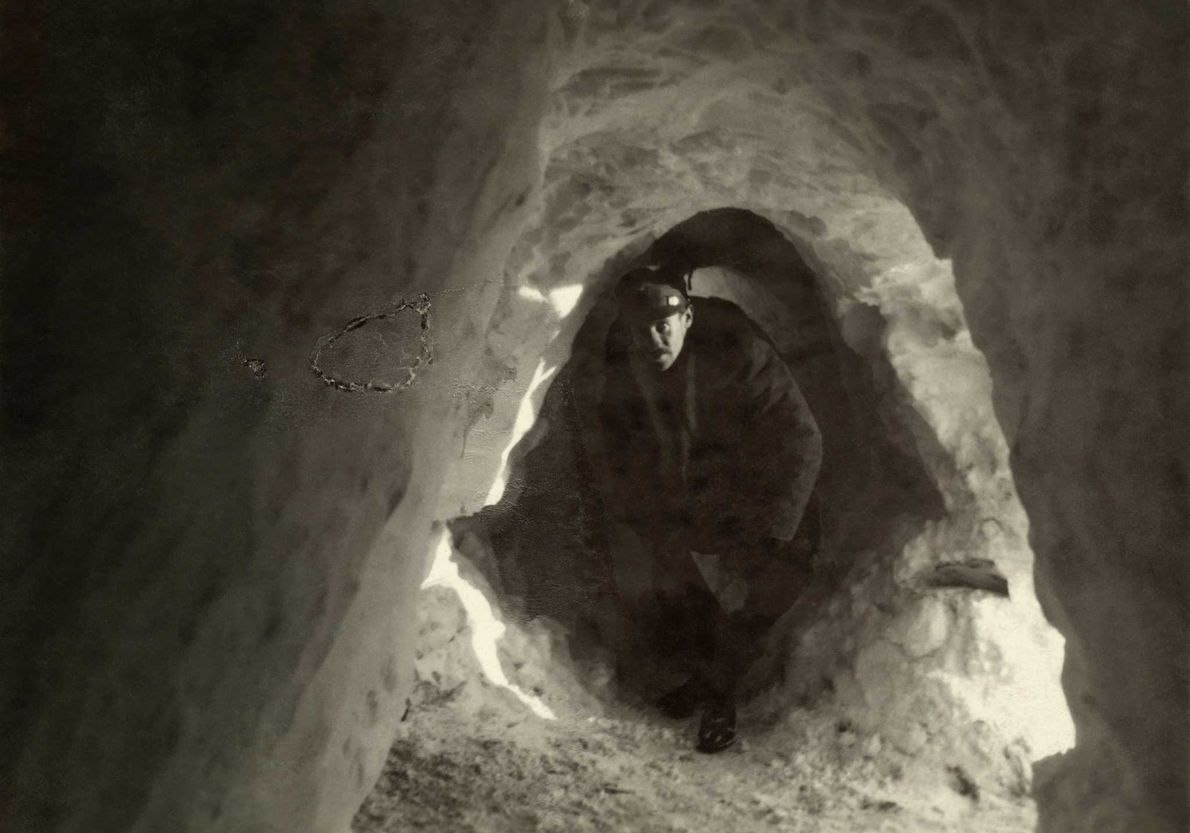 An Italian soldier crouches in a fully enclosed World War I snow trench.