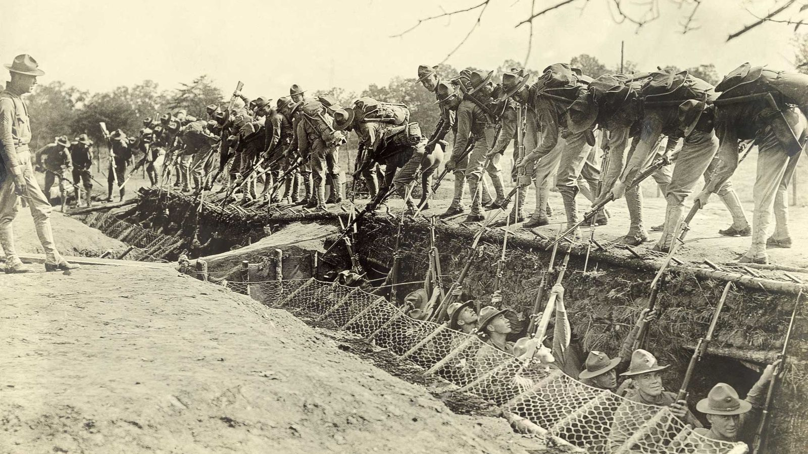 Training at Quantico, Virginia before deployment, United States Marines practice attacking and defending trenches.